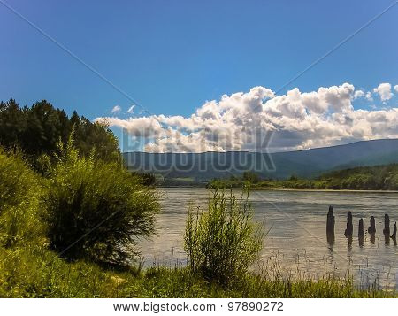 Irkut River in the midst of green bushes blue sky and mountains, Siberia ** Note: Visible grain at 100%, best at smaller sizes