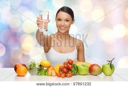 people, diet and vegetarian concept - happy asian woman with healthy food showing glass of water over blue lights background