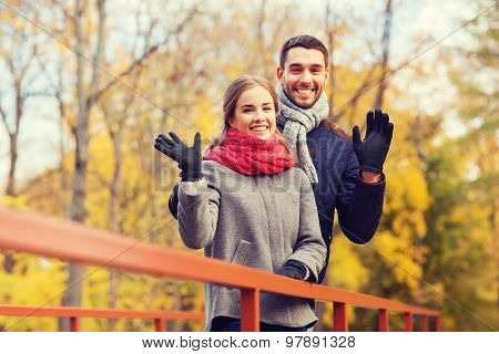 love, gesture, family, season and people concept - smiling couple hugging on bridge in autumn park