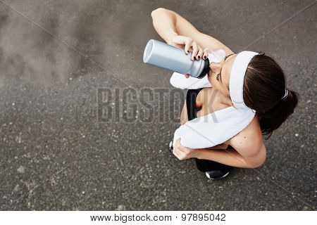 Active girl drinking water after workout