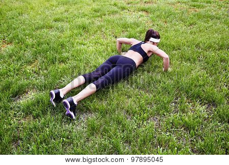 Fit young woman practicing pushups outdoors