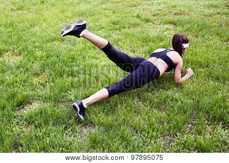 Fit girl practicing pushups on grass