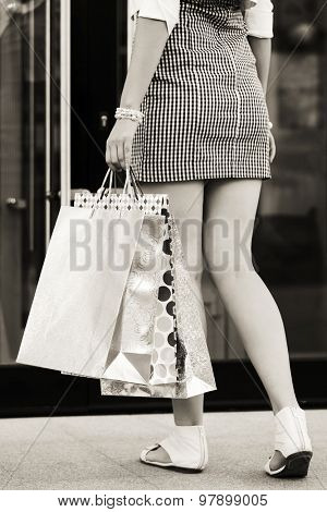 Woman with shopping bags at the mall doorway