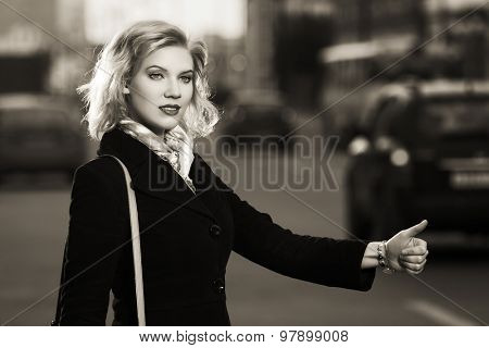 Young fashion woman hailing a taxi cab on city street