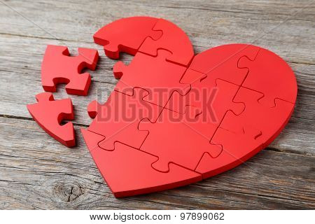 Red Puzzle Heart On wooden background, close up