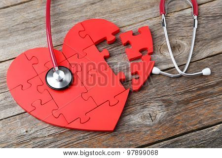 Red Puzzle Heart With Stethoscope On Grey Wooden Background