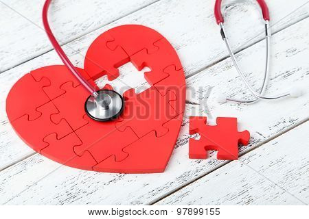 Red Puzzle Heart With Stethoscope On White Wooden Background