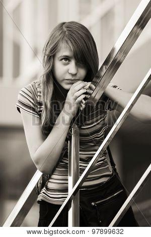 Sad teen girl against a school building