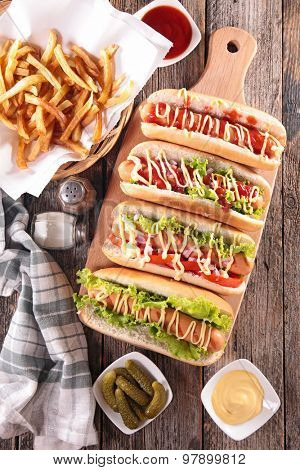 hot dog on board with sauce and french fries