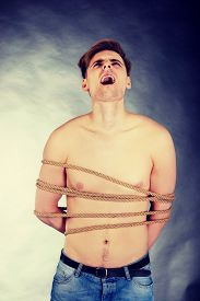 stock photo of torture  - Tortured shirtless man tied with a rope - JPG