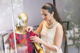 image of dress mannequin  - Beautiful brunette touching dress on the mannequin - JPG