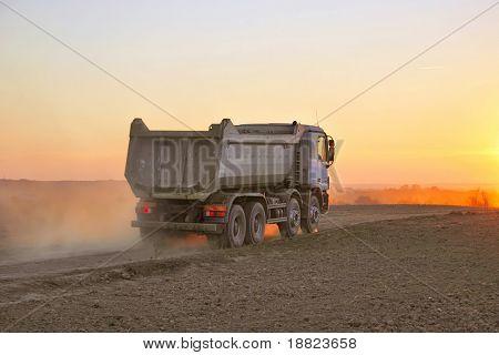 Schwere Lkw in staubiger Sonnenuntergang