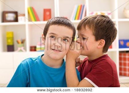 Two mischievous boys sharing a secret - closeup