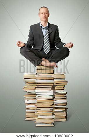 businessman in lotus pose with many books near isolated on white
