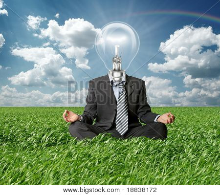 businessman in lotus pose and lamp-head in grass in green grass on blue summer sky