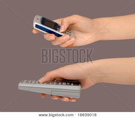 Feminino mão apontando com um controle remoto e discar o número de um telefone celular de gestos