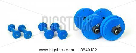 Three pairs of dumbbells from light to heavy isolated on white background - exercising concept