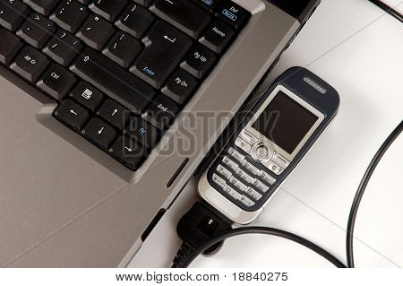 Cellphone connected to laptop computer wireless internet connection concept