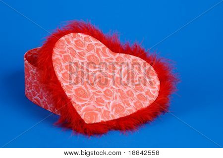 Lovely heart-shaped red fancy box isolated on blue background. Valentine's Day gift concept