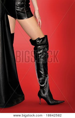 Sexy woman in leather outfit and black leather high stiletto boots Isolated silhouette on red background with clipping path