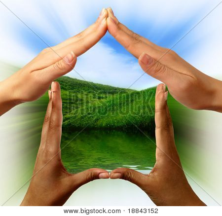 Conceptual symbol home made by black and white people hands framing the nature scenery