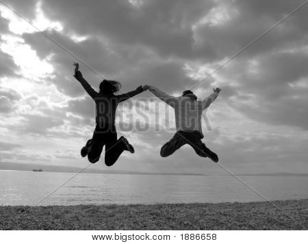 Happy Couple Jumping In The Beach