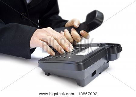 One hand pressing key on black phone