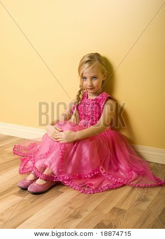Adorable little girl sitting in pink princess dress