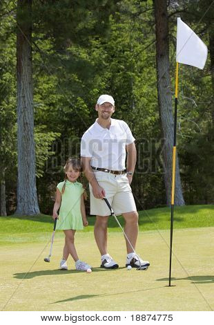 Full length view of father and young daughter standing on golf green.