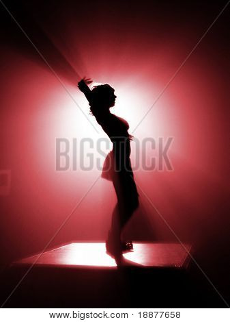 silhouette of disco dancer in red light