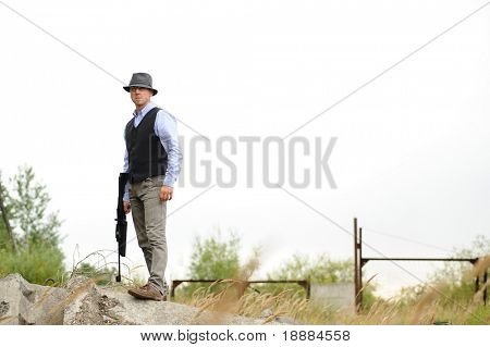 young gangster with rifle waiting for somebody