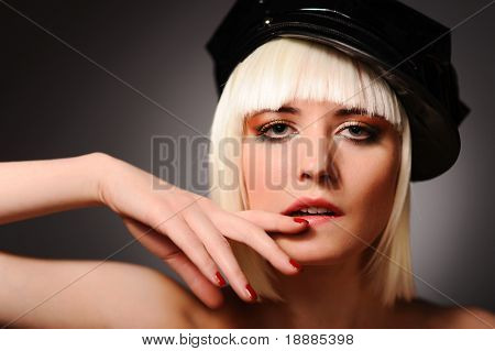 Close up portrait of sensuality model with blonde hair and black peaked cap, isolated on grey. may be use for fashion cards and posters