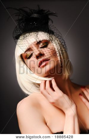 Close up portrait of sensuality model with blonde hair and black hat, isolated on grey. may be use for fashion cards and posters