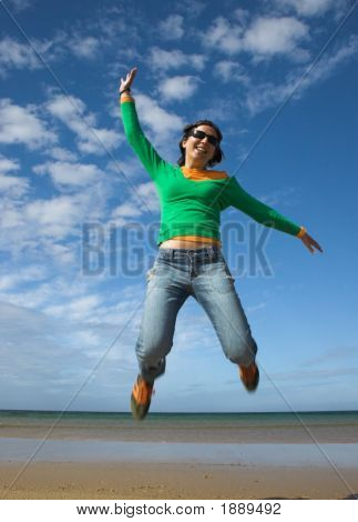 Young Beautiful Woman Making A Big Jump On The Beach