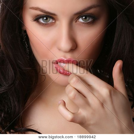 closeup of sexy female face with finger in mouth