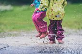 Children In Rubber Boots And Rain Clothes Jumping Puddle Defocused. poster
