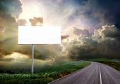 pic of road sign  - The road through the meadow and the stormy skies - JPG