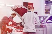 Automobile mechanics working in automobile repair shop poster