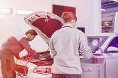 Automobile mechanics working in automobile repair shop poster