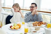 Naughty girl eating strawberry by table while young man looking at her poster