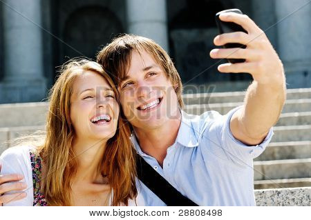 couple take a picture together while visiting a tourist attraction, smiling and having fun