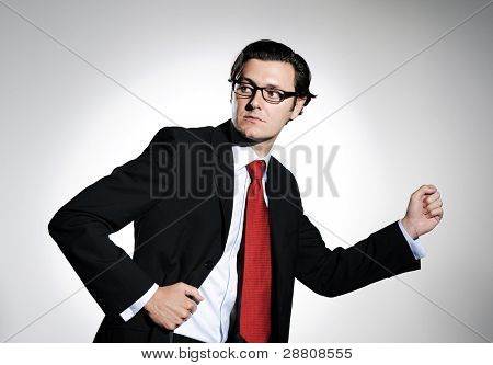 Businessman in suit looks back in studio with his arms raised like he is running