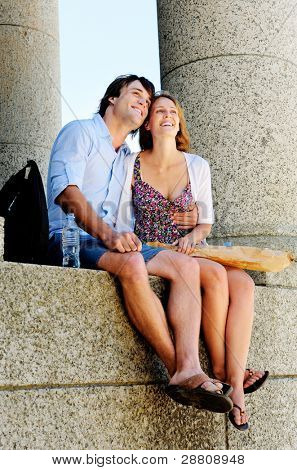 a tourist couple relaxes with some bread as they take in the sights of an old monument while they travel the worl