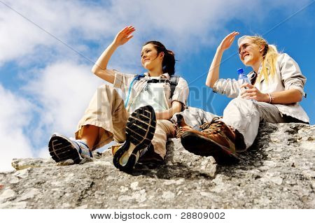 two women take a break from trekking and rest on a rock outdoors