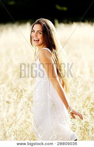 gorgeous girl walking in the field of long grass and dragging her hand touching the dry grass while laughing and smiling, carefree healthy lifestyle