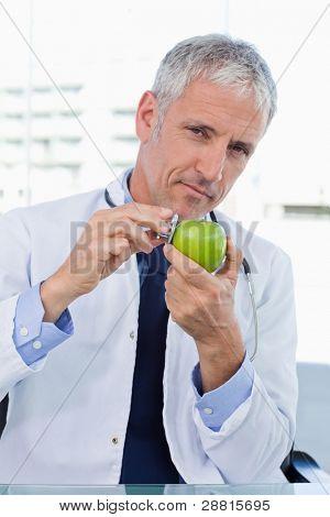 Portrait of a Doctor setzen seine Stethoskop auf einen Apfel in seinem Büro