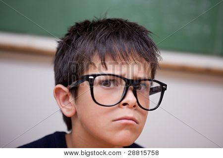 Close up of a serious schoolboy in a classroom