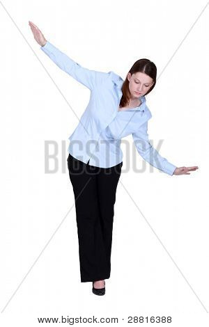 Woman walking an imaginary tightrope