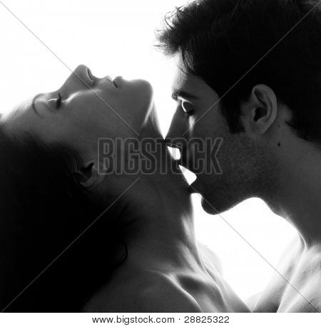 Passionate sensual attractive young couple in love, man caresses woman neck, isolated black and white portrait