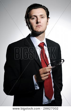 Handsome business owner with a red tie holds a pair of spectacles while in a relaxed stance, lit with dramatic lighting
